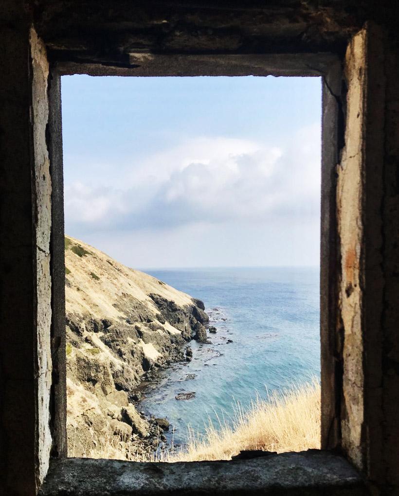 屋内から海岸線に続く荒涼とした岩肌を眺める